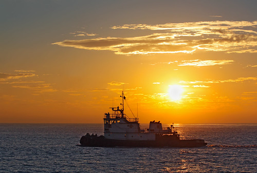 Silhouette of a tug boat at sunset. Photo taken during a whale-watching cruise by sgoodwin4813 via Flickr.