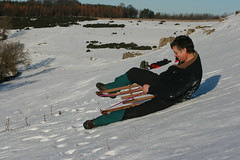 snowboarding(0.0), snowboard(0.0), sports equipment(0.0), winter sport(1.0), footwear(1.0), winter(1.0), vehicle(1.0), sports(1.0), snow(1.0), sledding(1.0), sled(1.0),