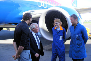 Government official meeting male and female apprentices in blue coveralls, in front of a jet engine.