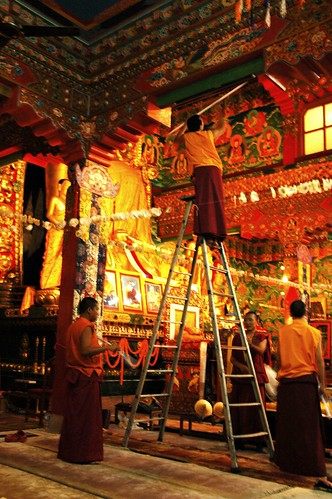 Monks replacing lights, redecorating for Bodhisattva Day, Tharlam Monastery of Tibetan Buddhism, Boudha, Kathmandu, Nepal by Wonderlane