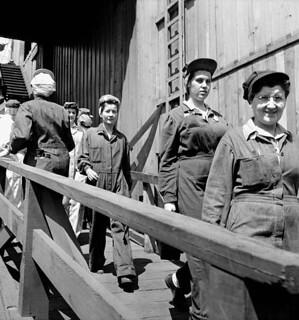 Female shipyard workers walking down a path returning to work after a 30-minute lunch break in the shipyard cafeteria / Des ouvrières retournent au travail à pied après leur pause-repas de 30 minutes à la cafétéria du chantier naval