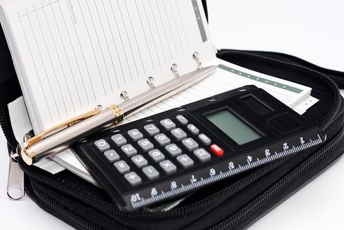 oggetti da ufficio: rubrica, penna e calcolatrice messi uno sopra l'altro
