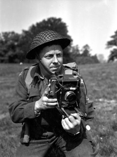 Lieutenant Frank L. Dubervill of the Canadian Army Film and Photo Unit, holding an Anniversary Speed Graphic camera, England, 11 May 1944. / Le lieutenant Frank L. Dubervill, de l'Unité de film et de photo de l'Armée canadienne, tient un appareil-photo An