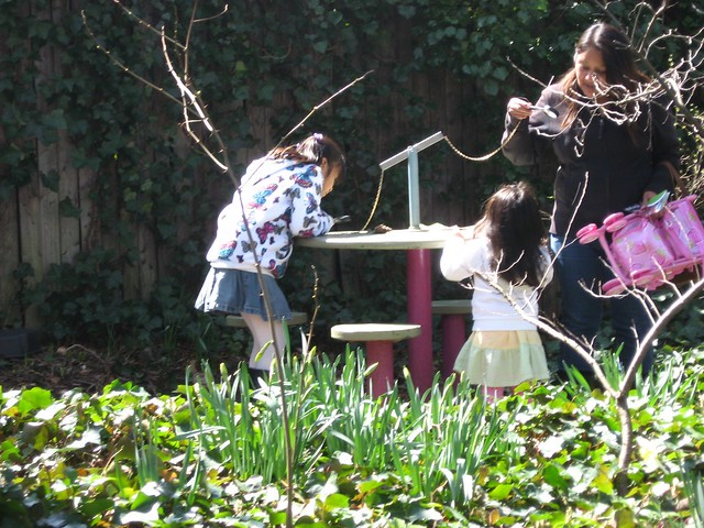 A family uses magnifying glasses to explore natural objects at one of the science tables. Photo by Ashley Gamell.