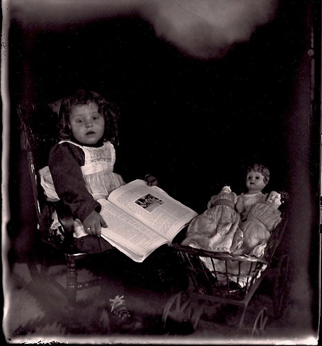 Little girl with book and dolls by sctatepdx