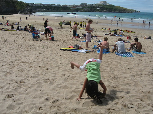 Girl doing cartwheels at the beach in Newquay, Cornwall