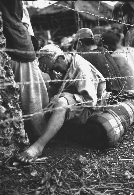 This disconsolate Japanese prisoner of war sits dejectedly behind barbed wire after he and some 306 others were captured within the last 24 hours of the Okinawa battle by Sixth Marine Division.  Okinawa, June 1945.  A. F. Hager, Jr.
