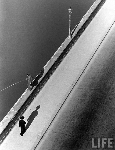 Sunday morning along the Arno River. A man fishing. A passerby casting a shadow, Florence, Italy 1935, by Alfred Eisenstaedt
