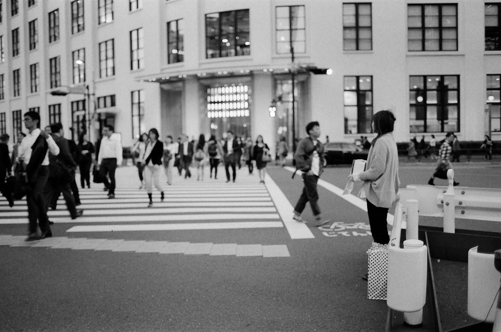 東京車站 Tokyo, Japan / Kodak TRI-X / Nikon FM2 模模糊糊的不是因為沒有對到焦,而是那時候已經是傍晚了,慢速快門造成的手震。  對面就是東京中央郵便局,忘記自己是前往還是回程了。  她在募款,但好像有點沒有印象是什麼募款,但一直覺得好像是在幫年輕媽媽養育小孩費用的募款。  不是很清楚,只是閃過這個想法。  Nikon FM2 Nikon AI AF Nikkor 35mm F/2D Kodak TRI-X 400 / 400TX 1275-0031 2015-10-06 Photo by Toomore