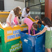 members of school's Environmental Club transferring paper from recycling bin to large dumpster