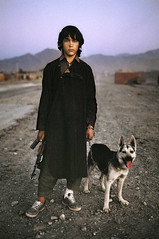 Afghan boy soldier waits for a ride on the road to Kandahar, Afghanistan, 1992, by Steve McCurry