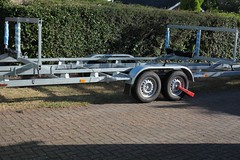 bass boat(0.0), bumper(0.0), automotive exterior(1.0), wheel(1.0), vehicle(1.0), boat trailer(1.0), trailer(1.0), land vehicle(1.0), chassis(1.0),