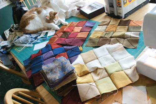 Tenzing, my ever-faithful snoozer, keeps the far side of the table from floating away while I sew square sets. All fabric in this quilt top hails from lightweight drapery and upholstery sample books, which I disassembled, removed the glued-on paper backings, and washed to ready for sewing.  Blog entry: domesticat.net/2010/08/square-dance