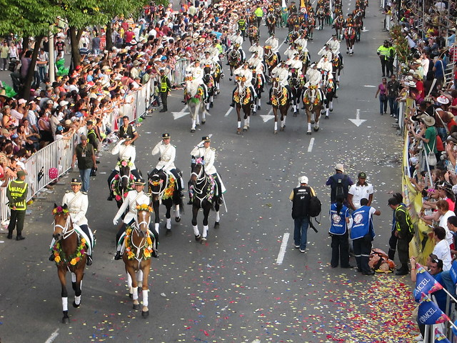 Military on horseback, as a woman who may have been suffering from exhaustion is carried away on a stretcher (right side).