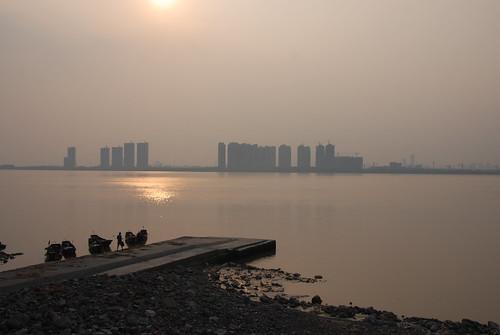 錢塘江畔蕭山農村的夕陽VS遠方的杭州市區都市高樓
