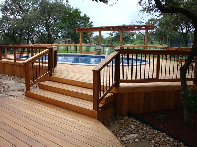 Oval above ground pool with wooden deck entrance bexar for Wood pool deck design