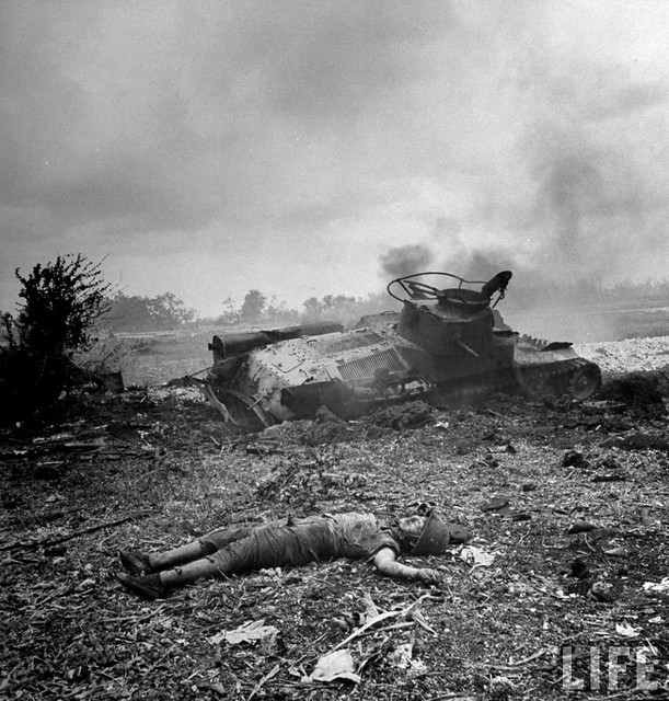 Corpse of Japanese soldier lies smoldering near his tank, which was knocked during fierce fighting w. US Marines during battle near town of Garapan, by Peter Stackpole 1944