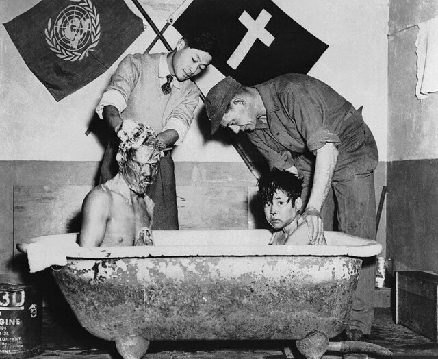 Men wash a pair of war orphan brothers in Korea, the boy on the left has been blind since birth, the UN set up orphanages to help alleviate some of the misery, 1952