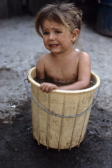 A young mennonite farm girl takes a bath in a bucket at home in Filadelphia, Paraguay, 1986, by Steve McCurry