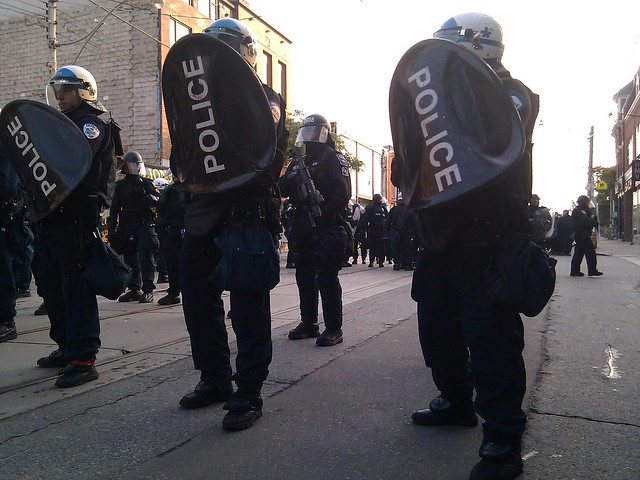 Riot police with shields and tear gas guns