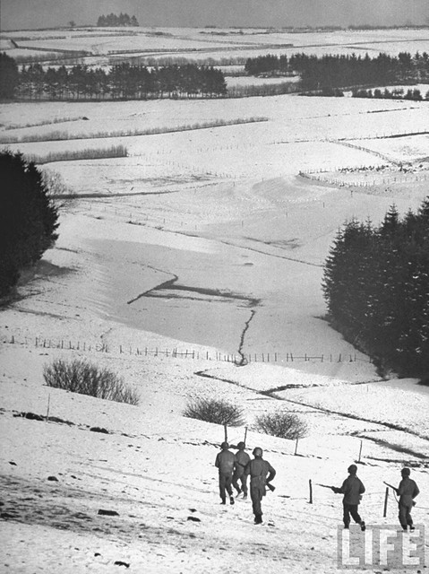 GIs setting out over snow-covered fields towards woods where German paratroopers are thought to be hiding, during the Battle of the Bulge, by George Silk 1945
