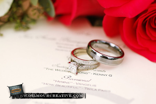 A Pair of Wedding Rings resting on the wedding program with red roses in the