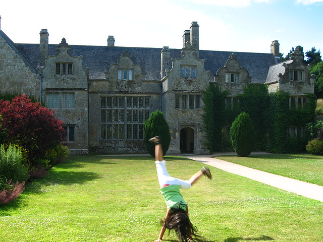 Girl doing cartwheels in the gardens at Trerice Manor, Cornwall