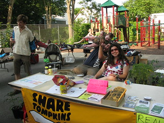 shira and a flying baby (and sitting daddy) at the share tompkins welcome table