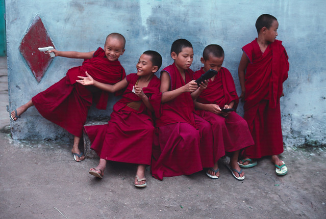 Young monks play with computer games in Sera Monastery in Bylakuppe, Southern India, 2001, by Steve McCurry