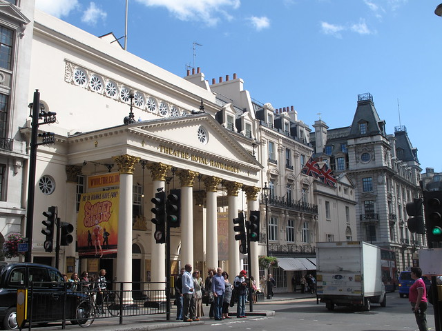 Theatre Royal Haymarket in London with blue sky UK flags & traffic light & people (closeup)