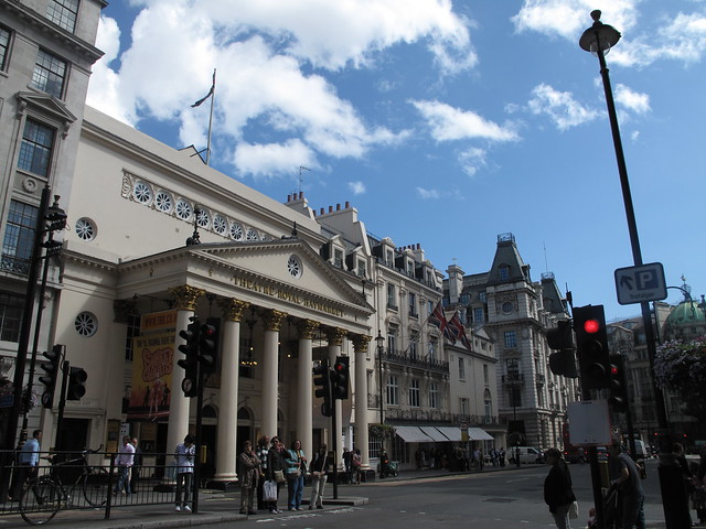 Theatre Royal Haymarket in London with blue sky UK flags & traffic light & people