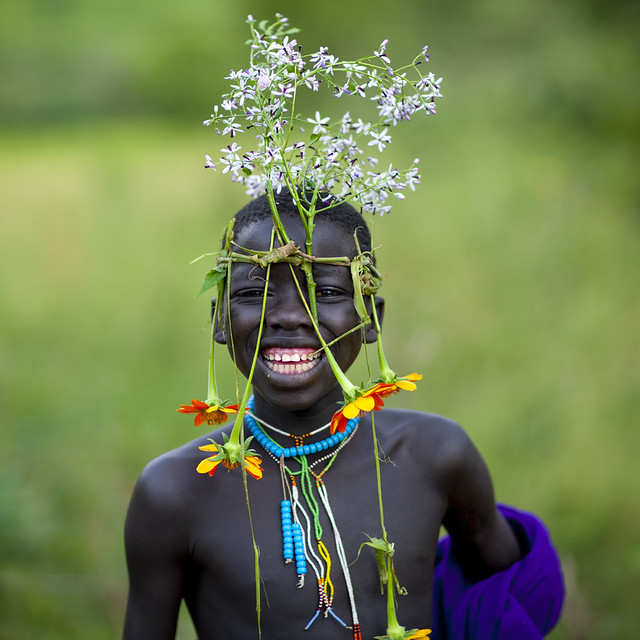 Surma tribe kid with flowers decoration - Omo Ethiopia - Tribes of the World