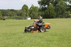 asphalt(0.0), agriculture(0.0), farm(0.0), soil(0.0), outdoor power equipment(1.0), field(1.0), grass(1.0), vehicle(1.0), mower(1.0), lawn mower(1.0), lawn(1.0), grassland(1.0),