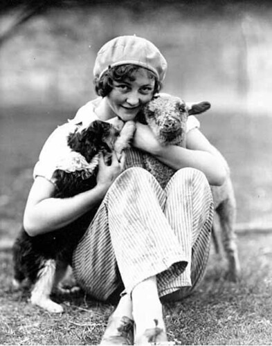 Girl wearing hat and pants seated in the grass holding a lamb and puppy, possibly Washington