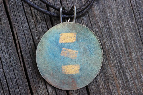 silver pendant with gold accents and patina