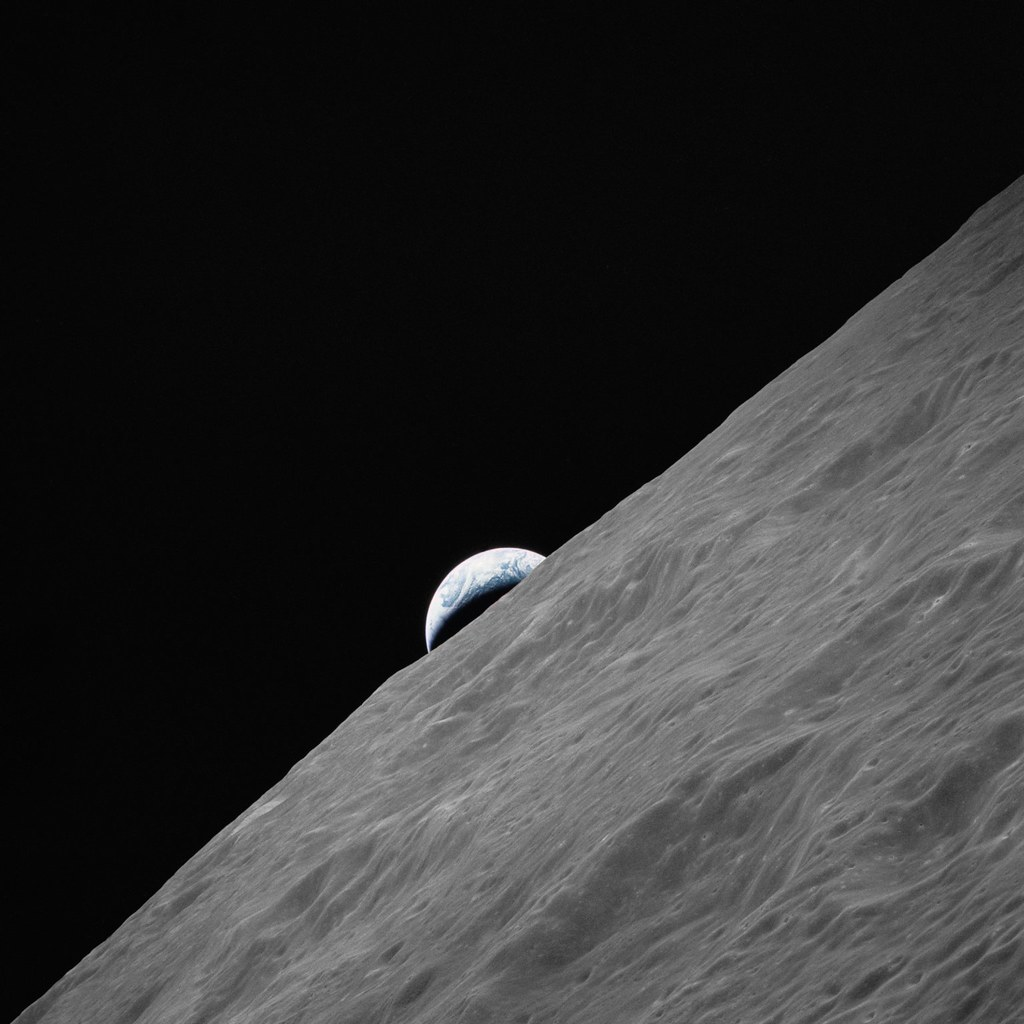 Cresent Earth rises above lunar horizon