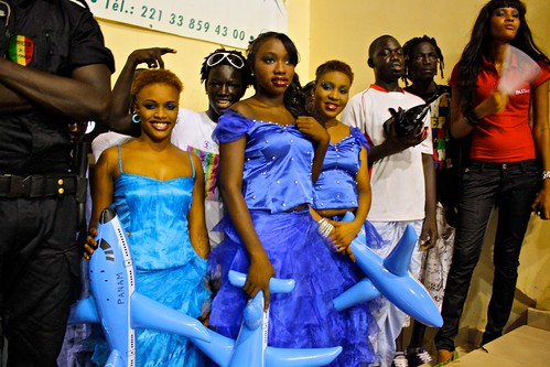<p>Oumou Sows entourage wait the turn on stage at Stade Demba Diop. They are holding inflatable airplanes to accessorize their dance and song about mobility.</p>