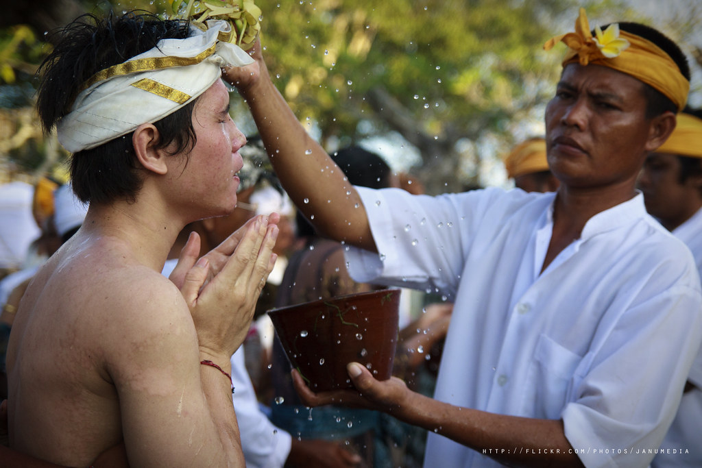image of balinese people using tirta (holy water) to wake up people from trance after doing sacred dance