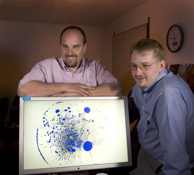 Alex Kent and Michael Fisk are helping Los Alamos National Laboratory (LANL) defend computer systems against malicious cyber attacks. The screen shows a graphic representation of attacks on Los Alamos National Laboratory (LANL). Blue and yellow splotches are clusters of computers' IP addresses that were attacked during an incident.  Photo by LeRoy Sanchez.