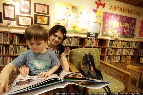 in the children's library   reading a book in mom's lap