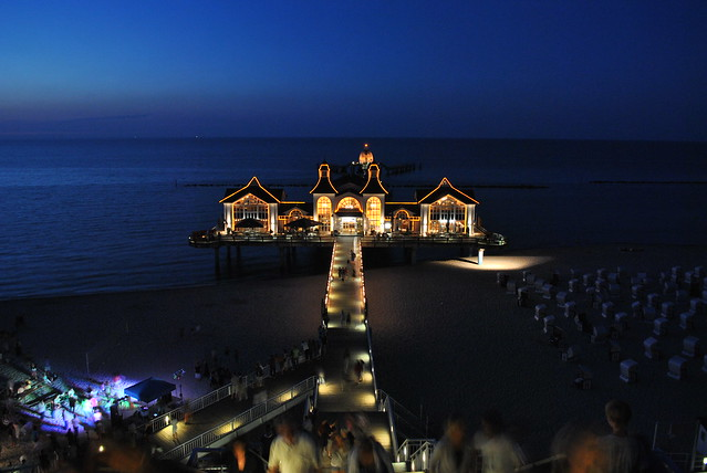Sellin Pier at Night with Beach Party /                                                                                         Nachtaufnahme der Seebrücke Sellin mit Beachparty