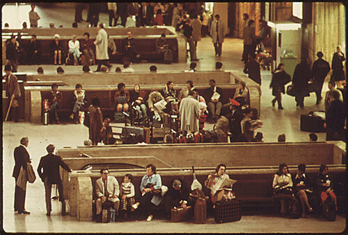 DOCUMERICA: Original Caption: Train passengers in the main hall of the 30th Street Station at Philadelphia, Pennsylvania. It is one of four or five stops made by Amtrak's Metroliners which made 16 round trips each day between New York City and Washington, District of Columbia. The corporation reported 18,000,000 passengers in the U.S. during 1974, an increase of 10 percent from the previous year. Despite more riders and revenue of $256.9 million, the management noted a deficit of $272.6 million, 04/1974 by Jim Pickerell.