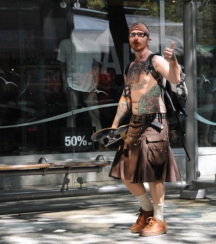 I see you too, Mod Scot Shaman, headscarf, glasses, beard, skateboard, utility kilt, belt, tatoos, piercing, pack, (Tatoos include fiery Totemic Owl, octopus, dog, and Salvador Dali's Face) Downtown Vancouver BC, Canada by Wonderlane