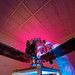 Scientist sees his reflection as he works on the Cibola satellite by Los Alamos National Laboratory