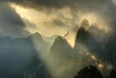 Rayons du soleil levant à travers les nuages au sommet des montagnes jaunes