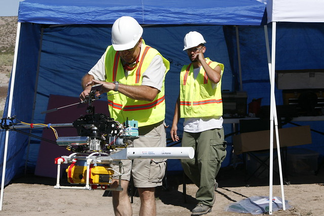 David Mascarenas (right) and Pilot Stan Johnson (left) prepare the RC helicopter with Structural Health Monitoring payload for field experiments on the Alamosa Canyon Bridge in New Mexico.  Photo by LeRoy Sanchez.