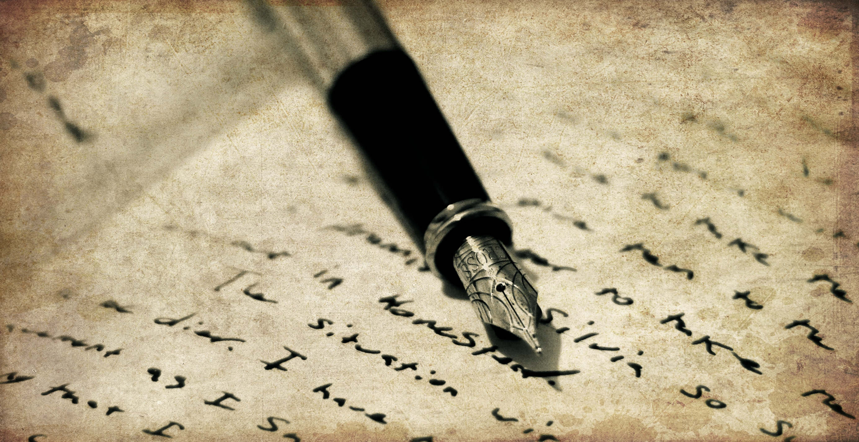 Picture of a brownish bacground with someones hand holding a pen, and writing