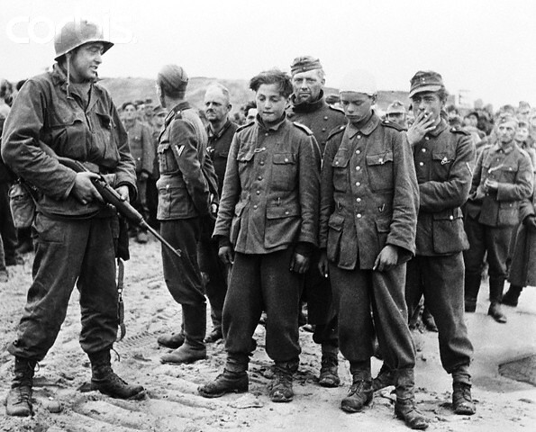 The two youngsters in the foreground were captured with Germans along the allied beachhead in Normandy.  While they appear to be about fourteen years old, they told their American captors they were eighteen.  Behind them are grizzled veterans taken in the