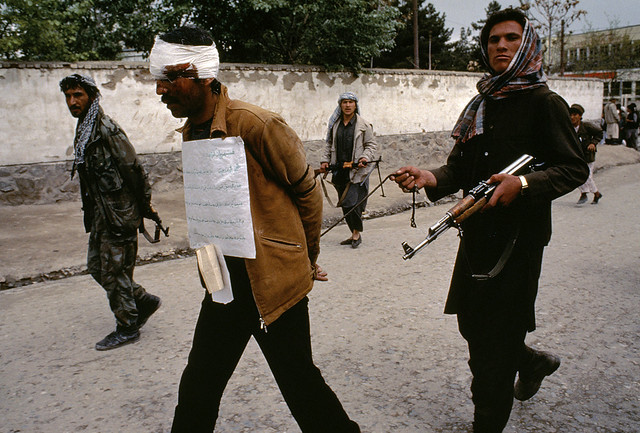 A mujahidin fighter parades a looter to jail, Kabul, Afghanistan, 1992, by Steve McCurry