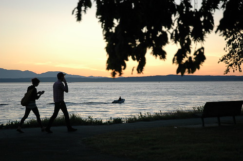 Cell phones in nature, a couple walking making calls, Golden Gardens Park, nightfall, boat, Seattle, Washington, USA by Wonderlane